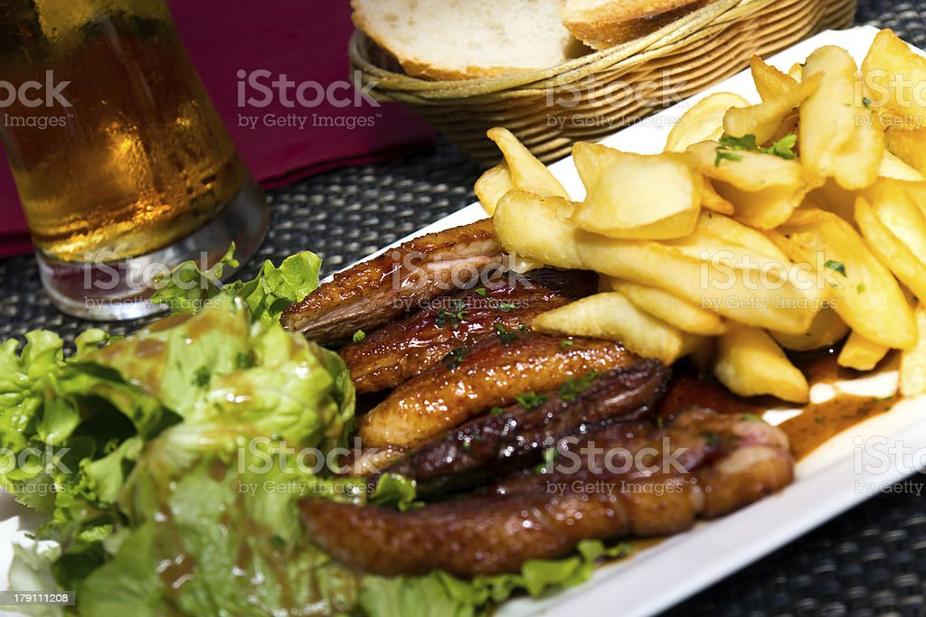Roasted duck with french fries, potatoes, caramelized, and Salad royalty-free stock photo