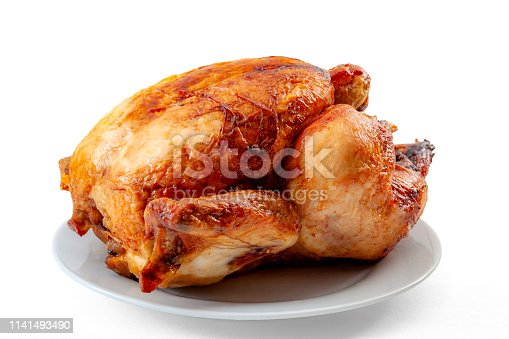 Roasted food and high protein dish concept with a whole roast chicken on a plain plate isolated on white background with a clipping path cut out