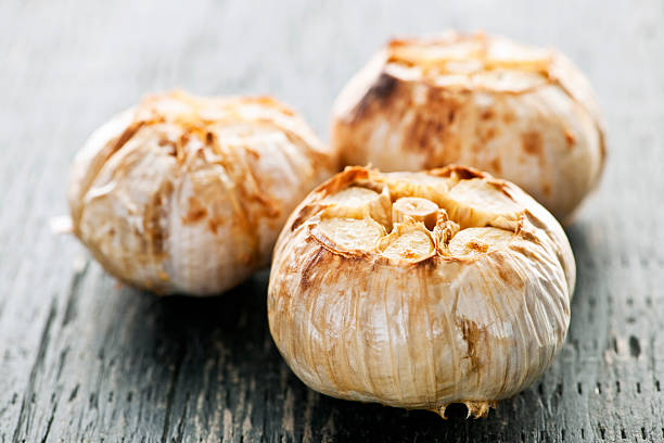 roasted garlic bulbs - garlic stock photos and pictures