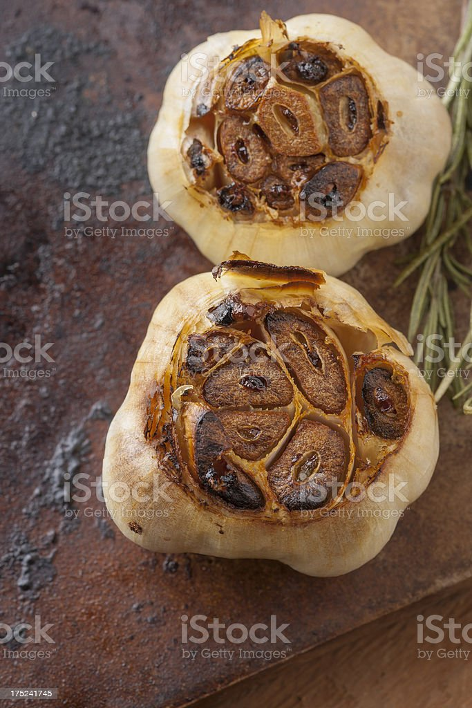 Roasted Garlic with Thyme on Stone Vertical stock photo