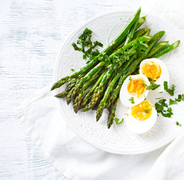 Roasted Green Asparagus with Boiled Eggs and Fresh Parsley stock photo