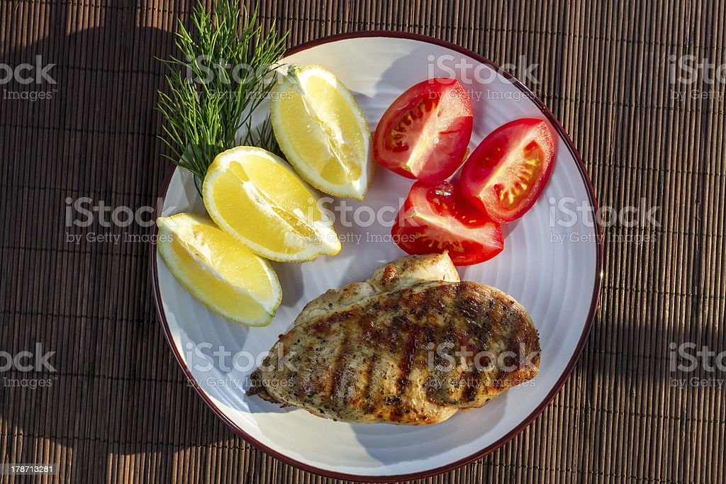 Roasted grilled chicken breast served with tomatoes royalty-free stock photo