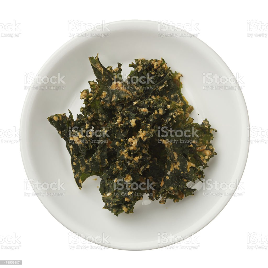 Roasted kale chips in a bowl isolated on white background royalty-free stock photo