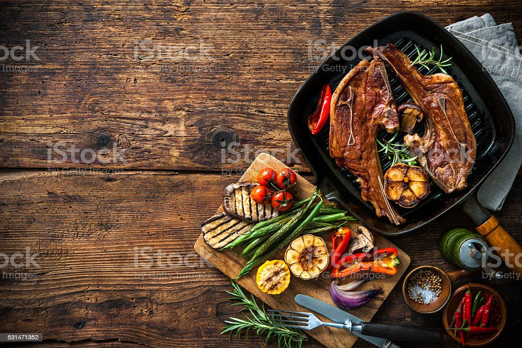 Roasted lamb meat with vegetables on grill pan foto
