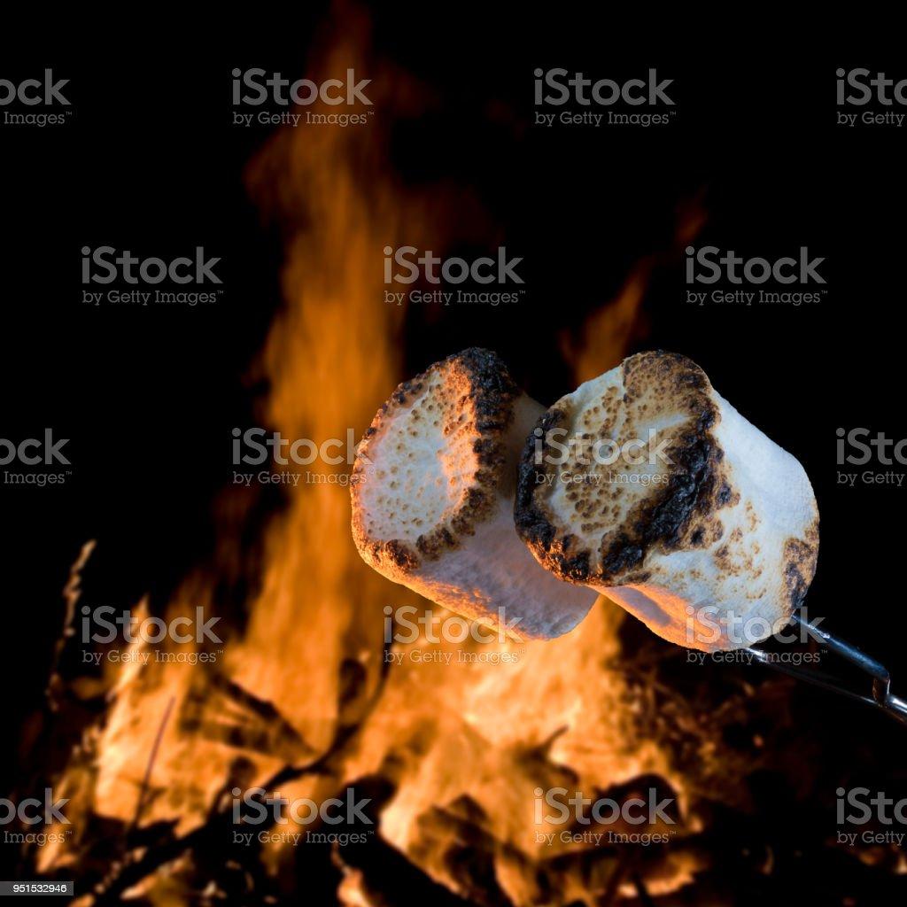 Geröstete Marshmallows mit einem Lagerfeuer hinter – Foto