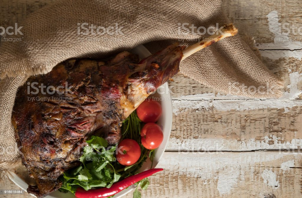 roasted meat leg of lamb baked whole lies with fresh tomato greens and hot pepper on a platter stock photo