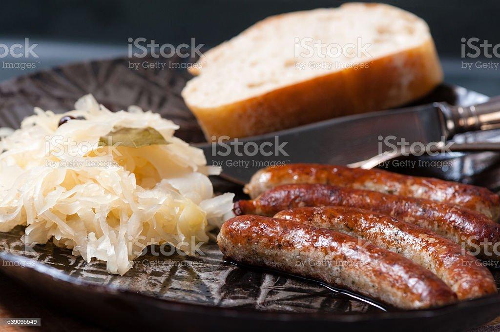 4 roasted Nuremberger Bratwurste/Sausages with Sauerkraut in an iron Pan stock photo