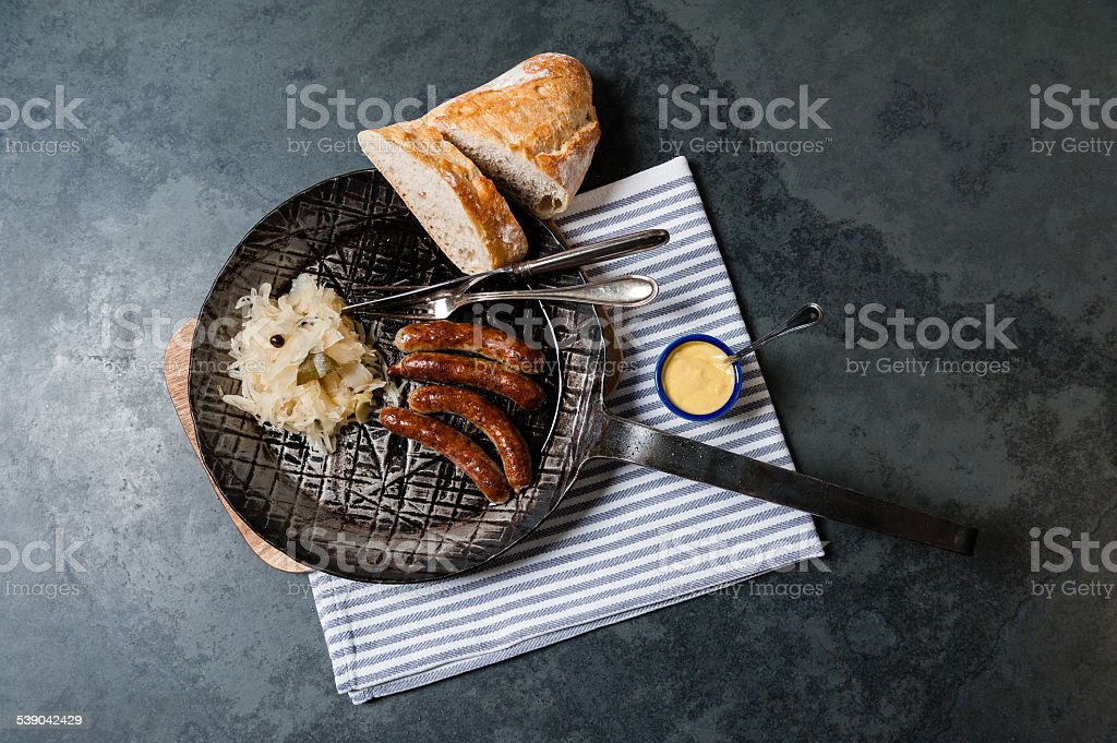 4 roasted Nuremberger Bratwurste/Sausages with Sauerkraut, seen from above. stock photo