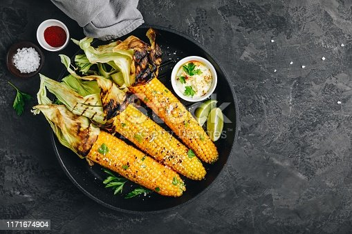 Roasted or grilled sweet corn cobs with garlic butter and lime. Mexican street corn on dark gray stone background, top view