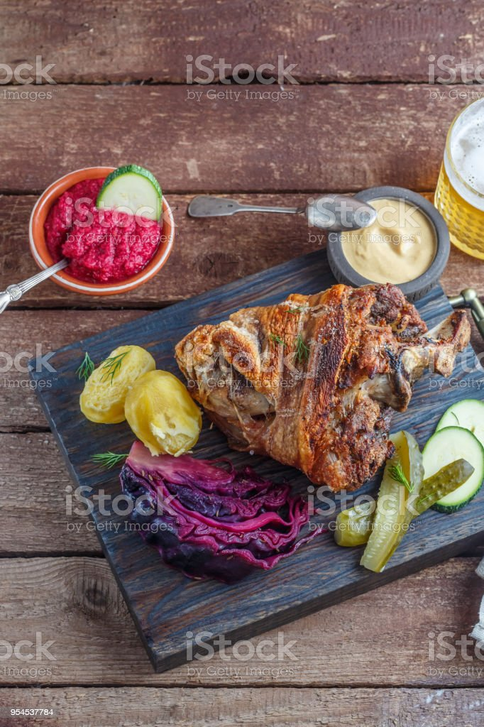 Roasted pork knuckle on black wooden board with appetizer and beer, copy space stock photo