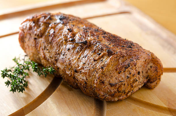 Roasted Pork Loin Boneless pork loin roast with a generous fat cap tied around it rests after roasting on a cutting board with thyme garnish.  Very shallow DOF. pork stock pictures, royalty-free photos & images