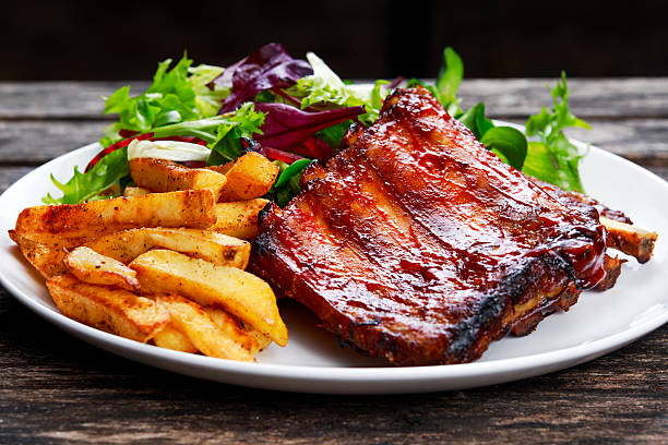 roasted pork rib, fried potato on white plate with vegetables. - rib voedsel stockfoto's en -beelden