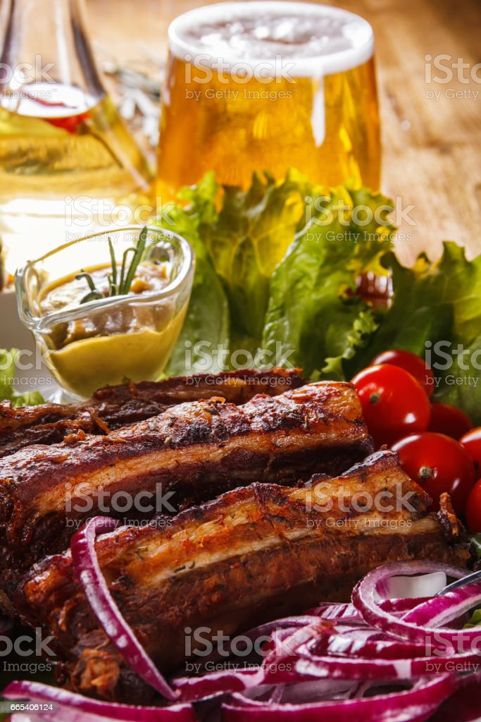 Roasted pork ribs, fresh vegetables and a glass of beer on a wooden table stock photo