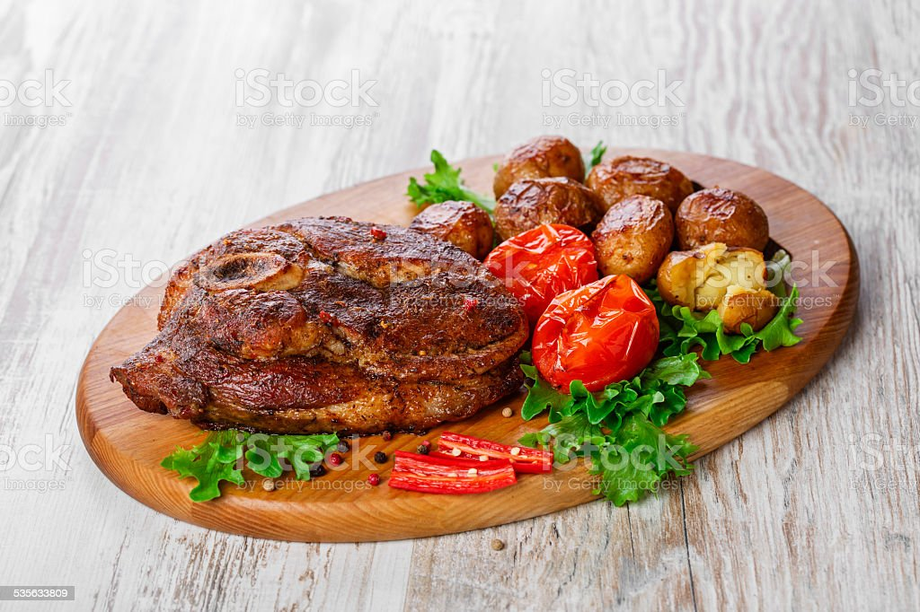 roasted pork shoulder on the bone with potatoes stock photo