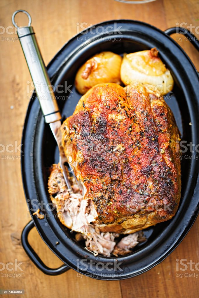 Roasted pork shoulder with onions in gravy stock photo