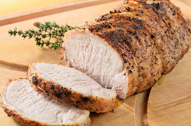 """Roasted Pork Tenderloin """"Herb crusted pork tenderloin roast being sliced on a cutting board, warm from the oven.  Thyme garnish.  Very shallow DOF."""" pork stock pictures, royalty-free photos & images"""