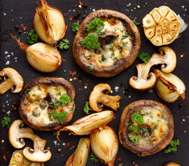 roasted portobello mushrooms stuffed with cheese and herbs on a black iron  background, top view. - cogumelos imagens e fotografias de stock