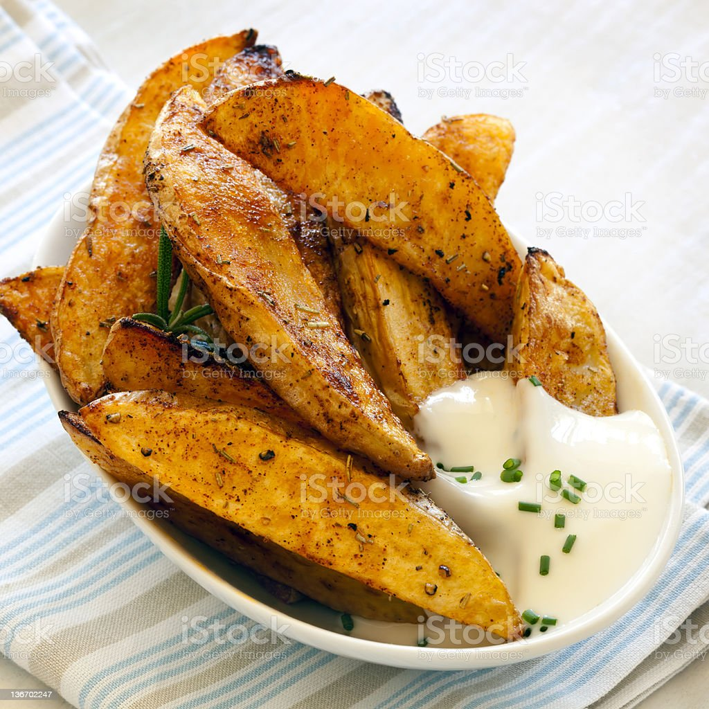 Roasted potato wedges with cheese dip on the side stock photo