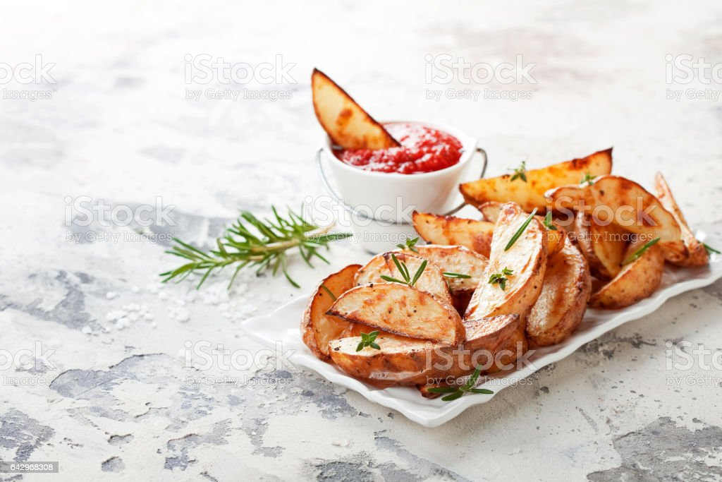 Roasted potato wedges with rosemary and tomato sauce stock photo