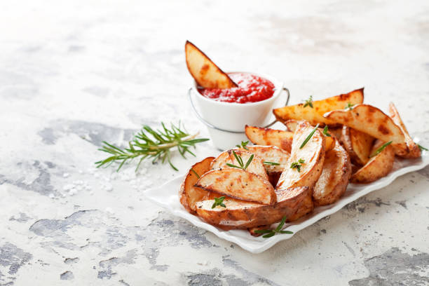 roasted potato wedges with rosemary and tomato sauce - knoblauchkartoffeln stock-fotos und bilder