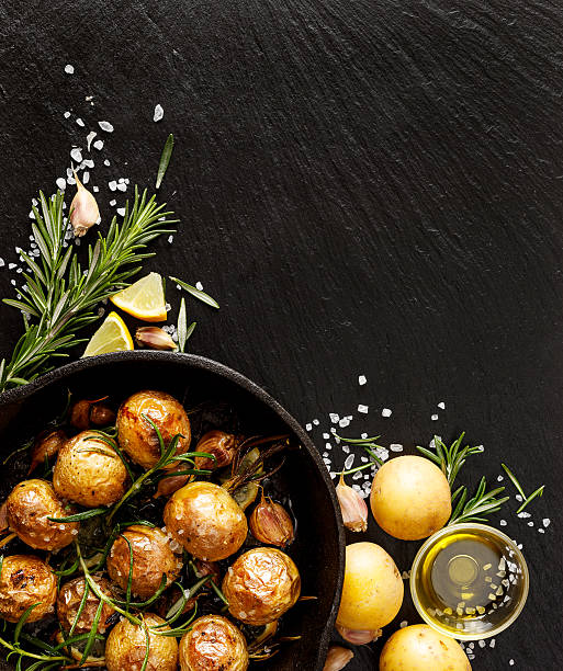 Roasted potatoes on a stone black background stock photo