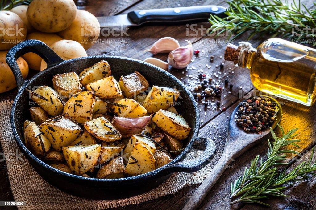 Roasted potatoes on wooden kitchen table stock photo