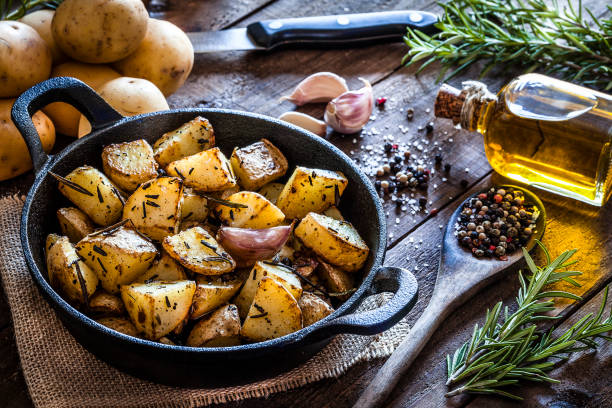 Roasted potatoes on wooden kitchen table stock photo