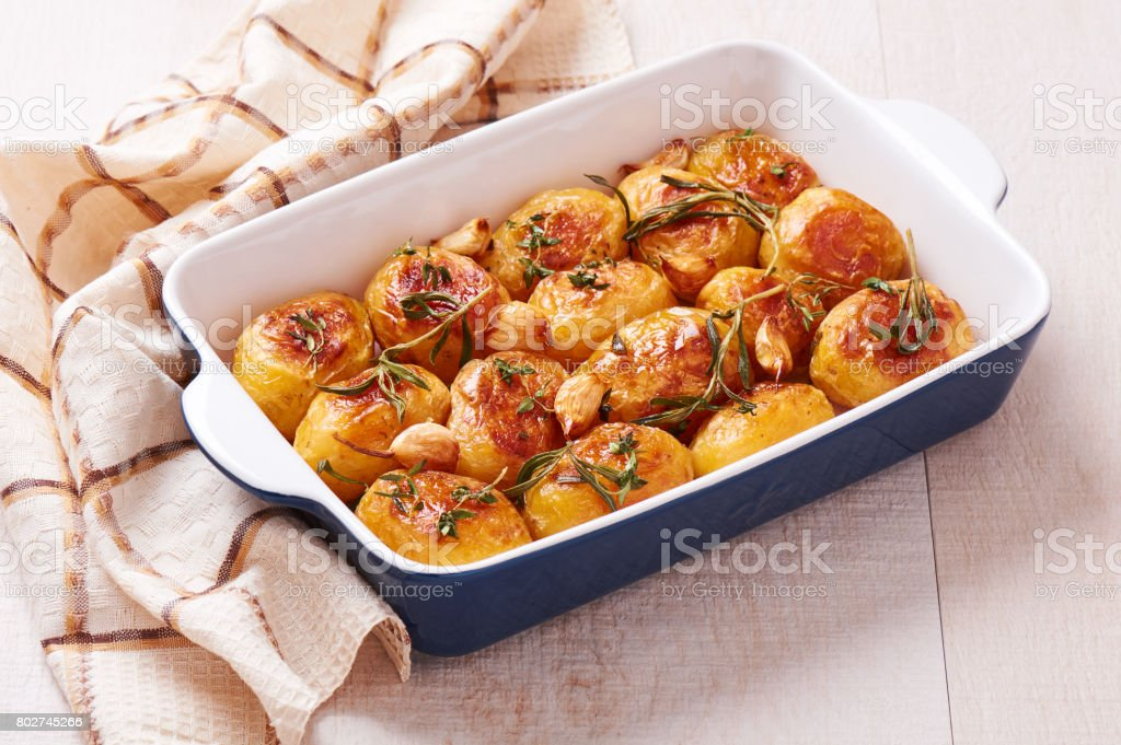 Roasted potatoes with garlic, thyme and rosemary in ceramic baking dish stock photo