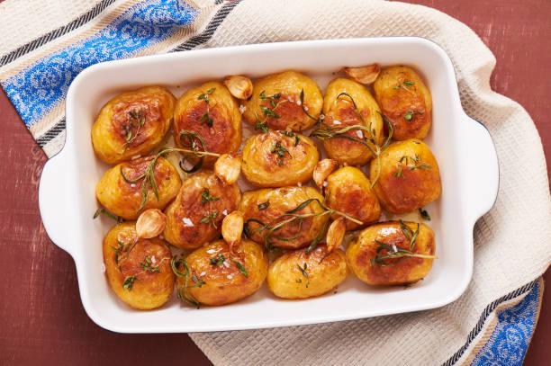 bratkartoffeln mit knoblauch, thymian und rosmarin in keramik auflaufform, ansicht von oben - knoblauchkartoffeln stock-fotos und bilder