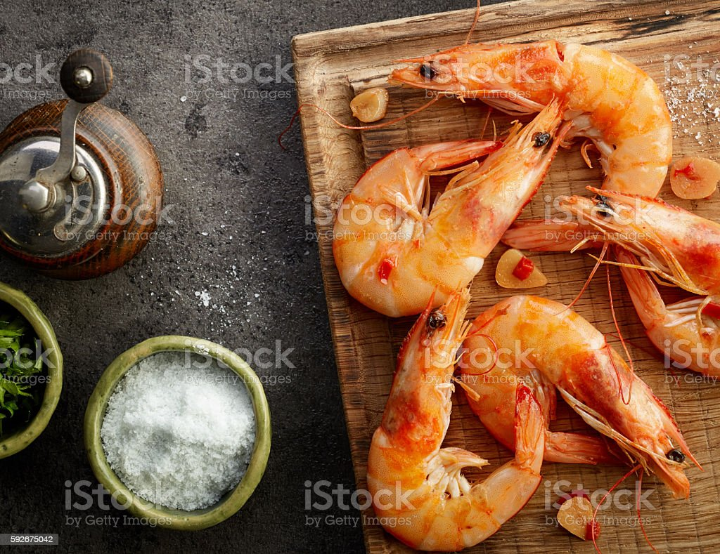 roasted prawns on wooden cutting board stock photo
