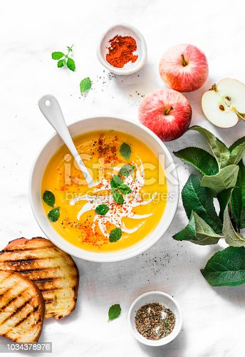 istock Roasted pumpkin and apples vegetarian soup on light background, top view. Flat lay. Healthy vegetarian food concept 1034378976