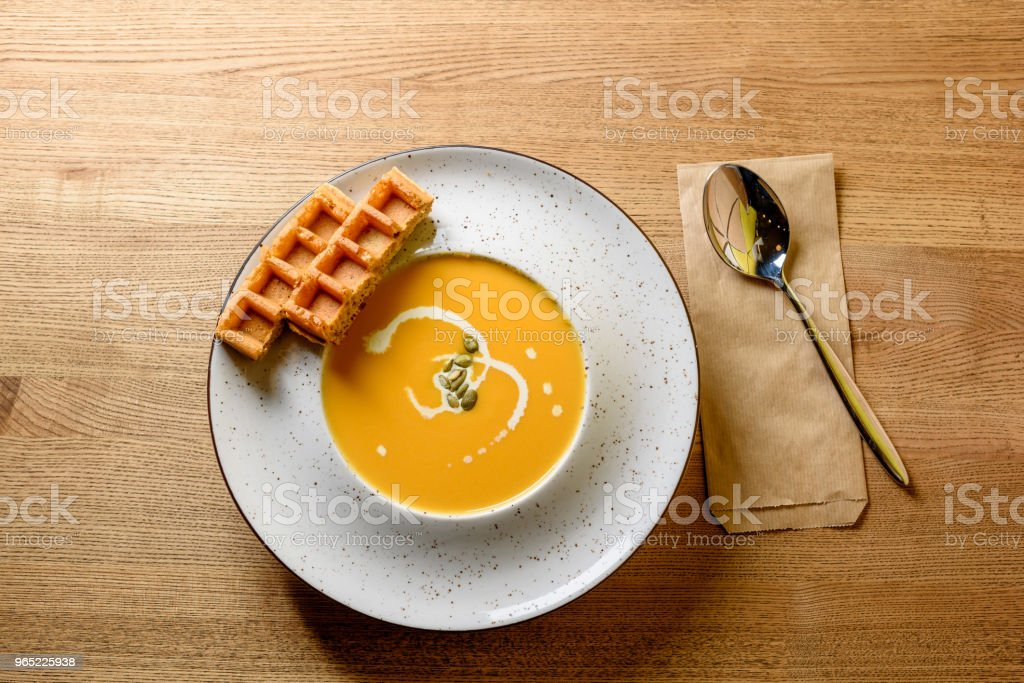 Roasted pumpkin and carrot soup with cream, pumpkin seeds and Belgian Waffle on wooden table background royalty-free stock photo