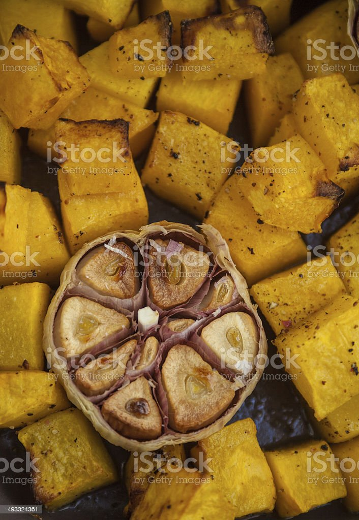 Roasted pumpkin cubes and half of garlic head stock photo