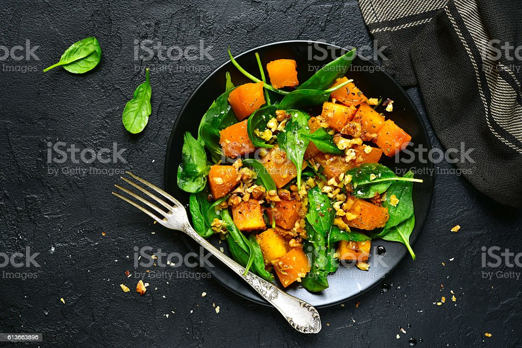 Roasted pumpkin salad with spinach and walnut .Top view. – Foto