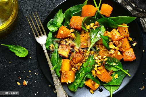 istock Roasted pumpkin salad with spinach and walnut .Top view. 613666608
