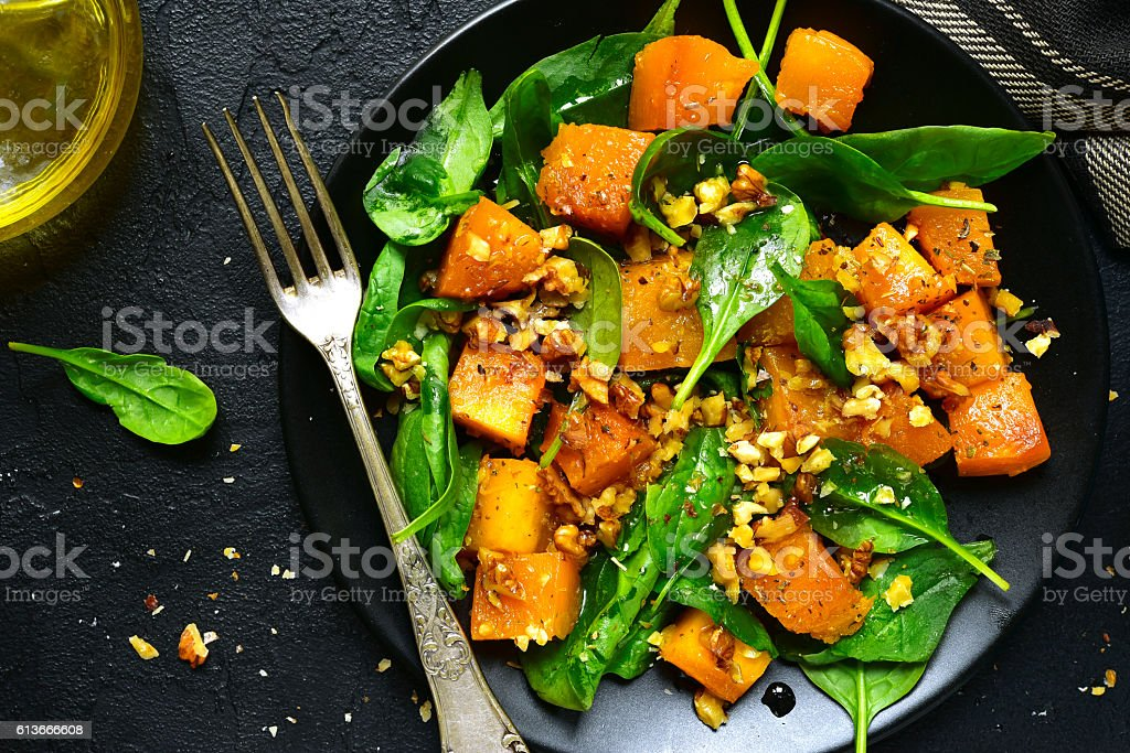 Roasted pumpkin salad with spinach and walnut .Top view. stock photo