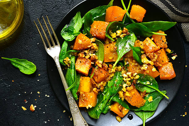 roasted pumpkin salad with spinach and walnut .top view. - vegetariano foto e immagini stock