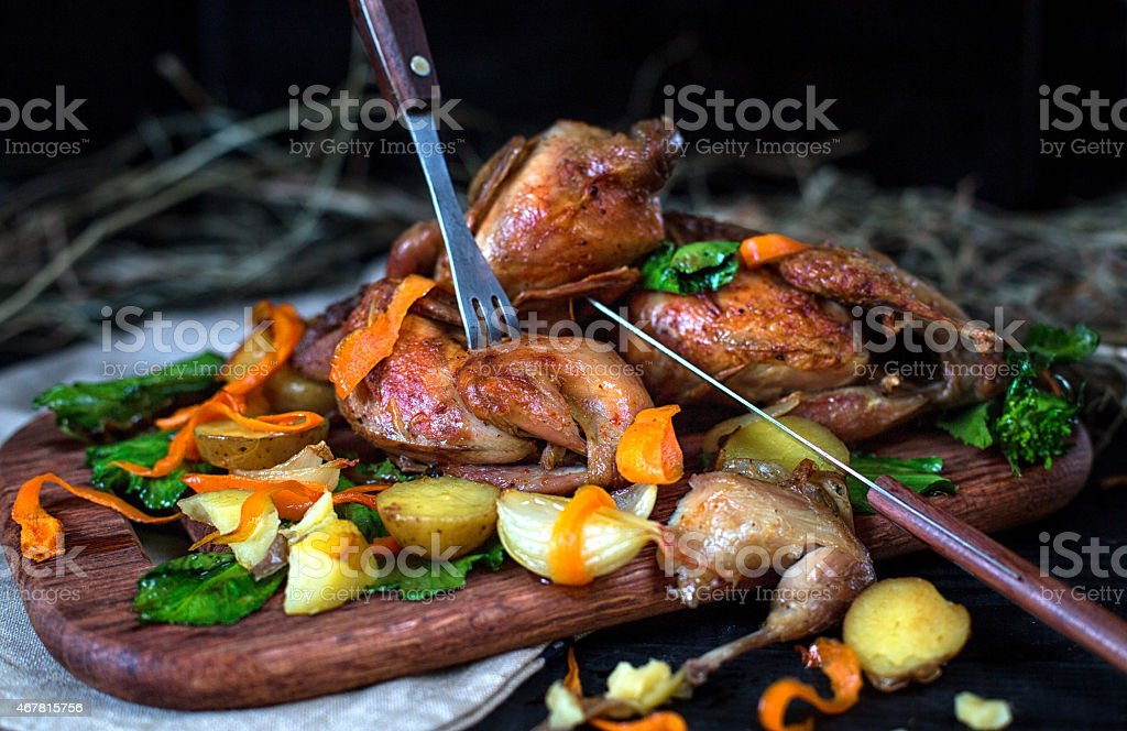 Roasted quails with vegetables on a wooden board stock photo