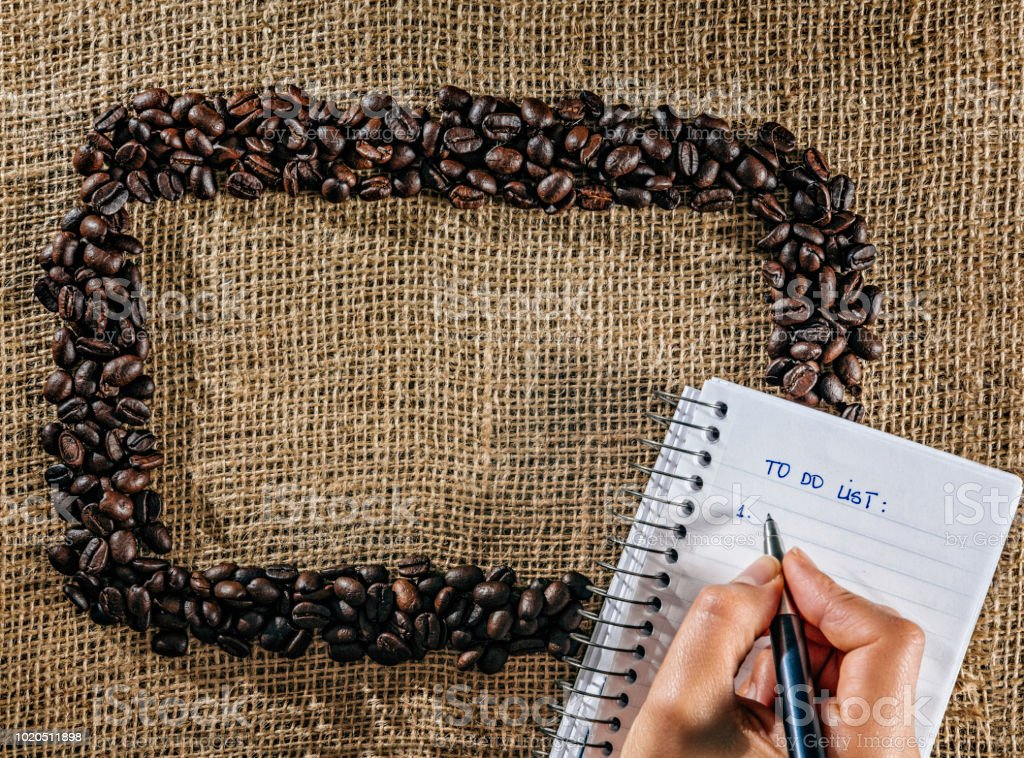 Roasted raw coffee beans making a frame on jute background with copy space stock photo