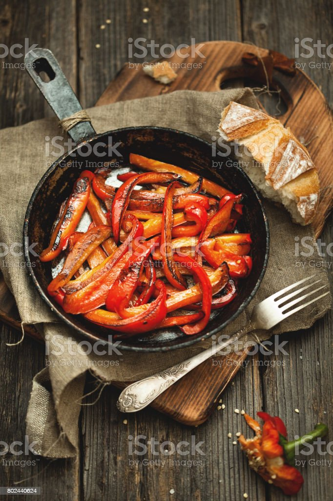 Roasted red pepper in cast iron frying pan on wooden table. stock photo