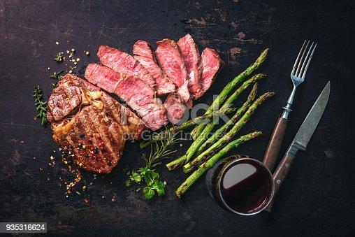 808351132 istock photo Roasted rib eye steak with green asparagus and wine 935316624