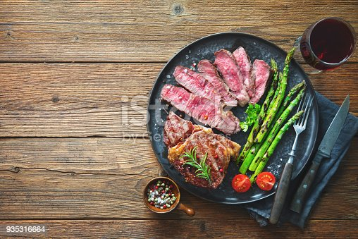 808351132 istock photo Roasted rib eye steak with green asparagus and wine 935316664