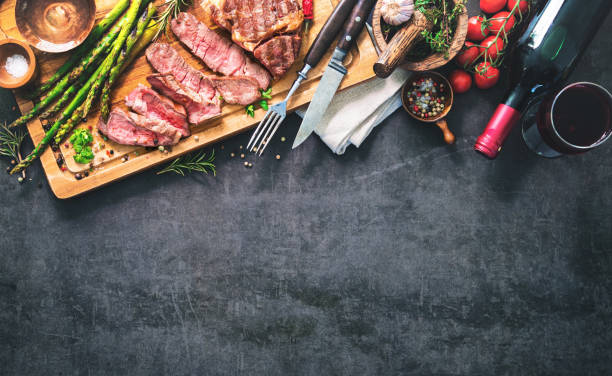 Roasted rib eye steak with green asparagus and wine stock photo