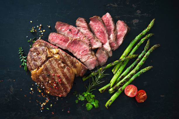 Roasted rib eye steak with green asparagus Roasted rib eye steak with green asparagus on old sheet roast beef stock pictures, royalty-free photos & images