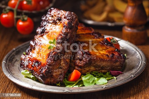 istock Roasted ribs, served on an old plate. Dark or balck background. 1157960546