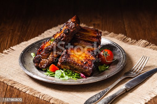 istock Roasted ribs, served on an old plate. Dark or balck background. 1157960820