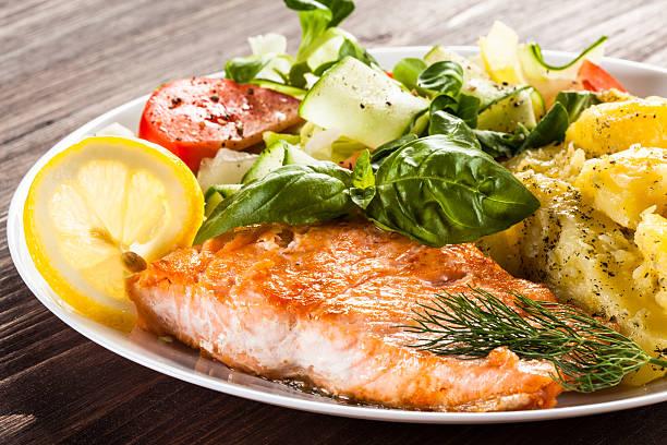 Legumes e salmão assado - foto de acervo