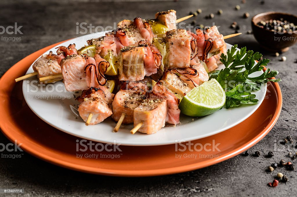 Roasted salmon skewers with bacon and lime stock photo
