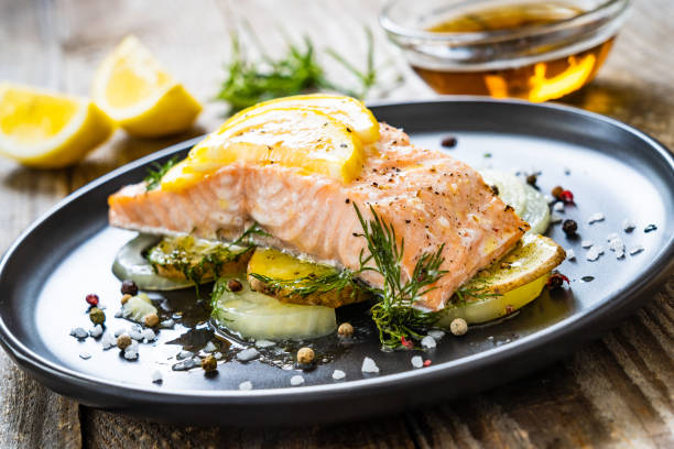 Roasted salmon steak served with lemon and onion on wooden table stock photo
