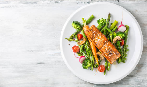 Roasted salmon steak with asparagos broccoli carrot tomatoes radish green beans and peas. Fish meal with fresh vegetable Roasted salmon steak with asparagos broccoli carrot tomatoes radish green beans and peas. Fish meal with fresh vegetable. main course stock pictures, royalty-free photos & images